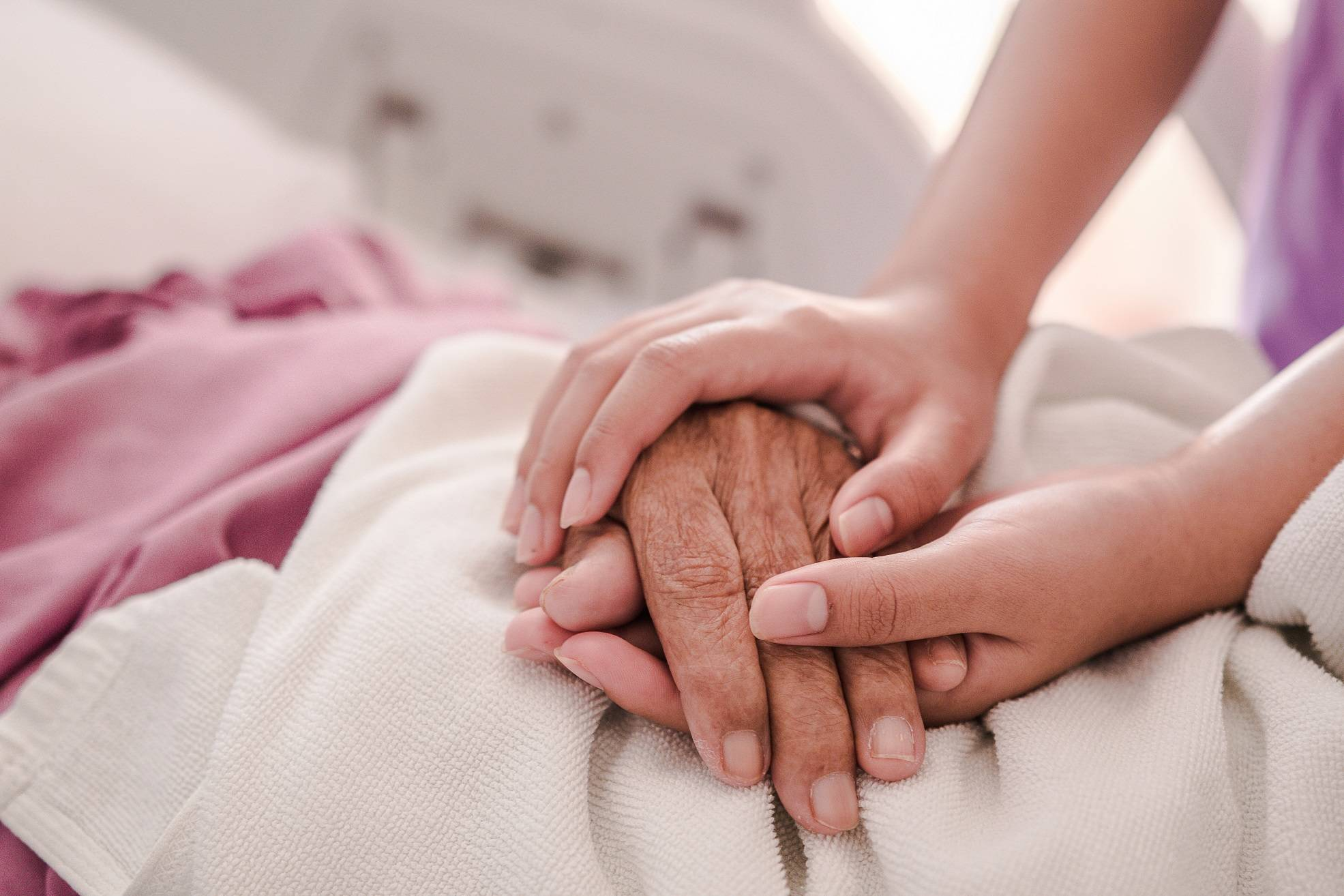 Young person holding hands with older person