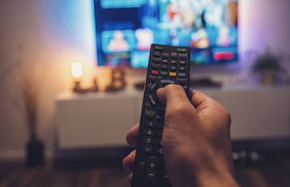 Man pointing remote at television