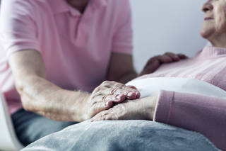 man touching the hand of older person lying in bed